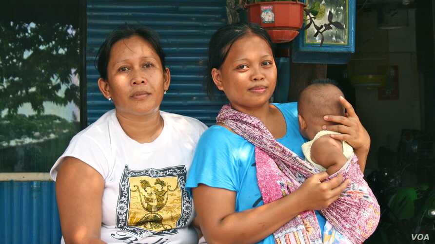 Santi with her four-month-old son and neighbor. The 26-year-old mother says she cannot afford birth registration for her children, Jakarta, Indonesia, March 2, 2013. (K. Lamb/VOA)