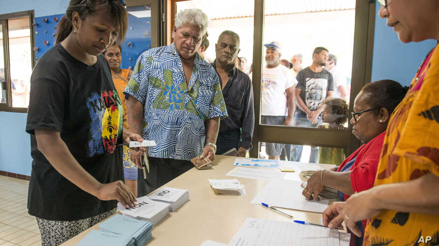 People line up at a polling station in Noumea, New Caledonia, as they prepare to cast their votes as part of an independence referendum, Nov. 4, 2018.