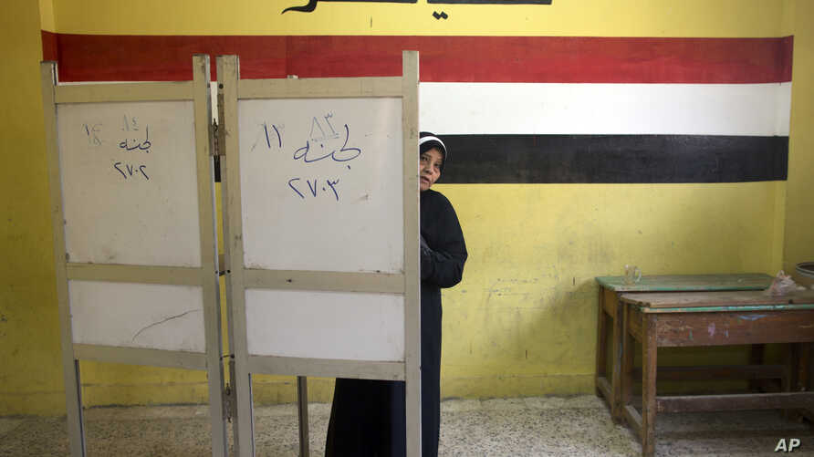 A woman prepares to vote during the second day of the presidential election at a polling station in Cairo, Egypt, Tuesday, March 27, 2018. Egyptians are voting for a second day in a lackluster election that President Abdel-Fattah el-Sissi is virtuall