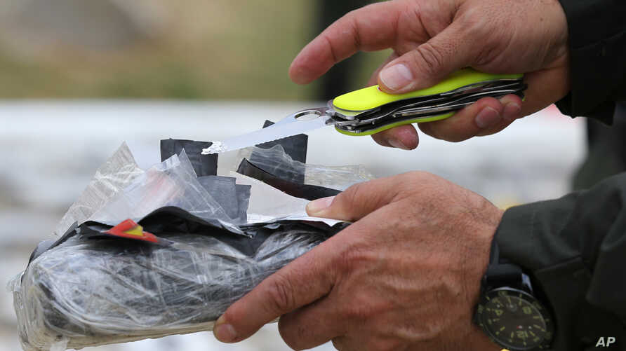 FILE - National Police Chief Gen. Rodolfo Palomino opens a package of seized cocaine to show to the press at a police station in Necocli, Colombia, Feb. 24, 2015.