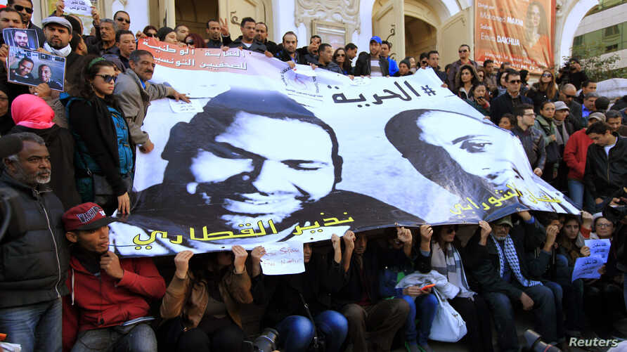 FILE - People hold a poster of journalists Nadhir Ktari (L, in poster) and Sofian Chourabi, who went missing in Libya in September, during a rally over their disappearance, in Tunis, Jan. 9, 2015.