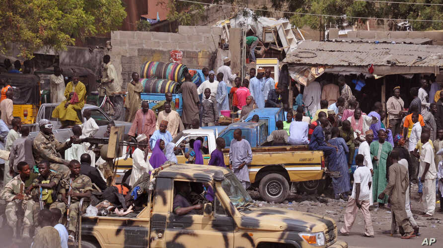 FILE - In this photo taken Jan. 27, 2015, Nigerian soldiers on a truck patrol at a market after recent violence in areas surrounding Maiduguri. In a major offensive against Boko Haram, Nigerian and Chadian jets are bombing the Islamic extremists from