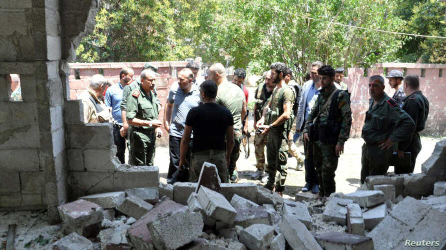 Army soldiers inspect the site of a suicide attack at a bus station in the government-held city of Hama in western Syria, in this handout picture provided by SANA on July 6, 2017, Syria.