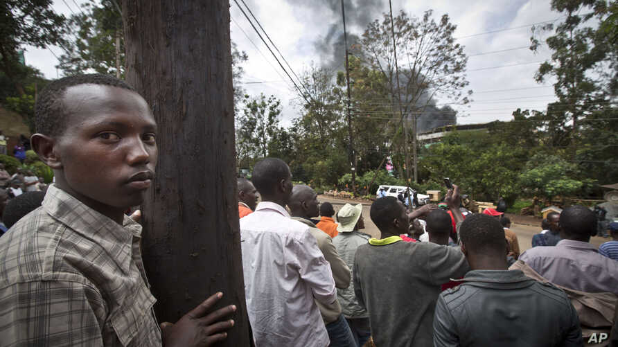 Onlookers observe from an overlooking hill as a plume of black smoke billows over the Westgate Mall, following large explosions and heavy gunfire, in Nairobi, Kenya, Sept. 23, 2013.
