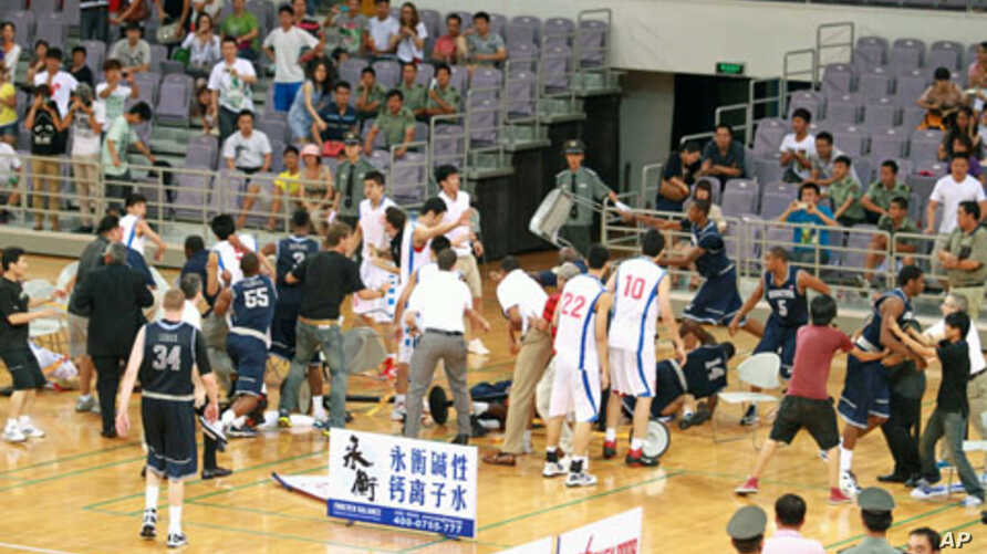 Basketball players from Georgetown University in Washington DC and China's Bayi team trade punches during their friendly game at the National Olympic Sports Center Gymnasium in Beijing, August 18, 2011