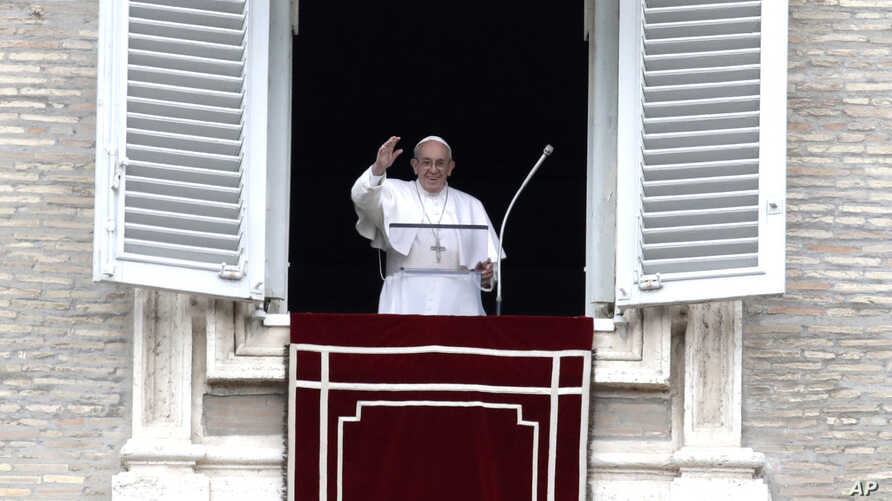 Pope Francis waves to the crowd as he arrives for the Angelus noon prayer from the window of his studio overlooking St.Peter's Square, at the Vatican, Feb. 25, 2018.
