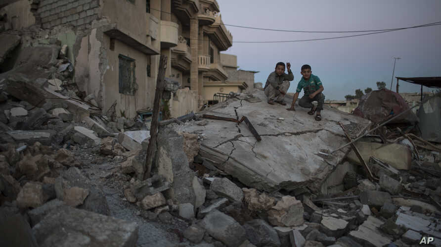 Two boys sit atop a destroyed house in a neighborhood recently retaken by Iraqi security forces from Islamic State militants, in west Mosul, Iraq, April 5, 2017.
