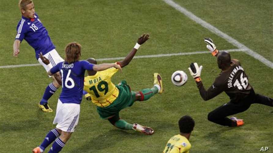 Japan's Keisuke Honda, top left, scores the opening goal against Cameroon goalkeeper Souleymanou Hamidou, right, and Cameroon's Stephane Mbia, third from left, during the World Cup group E soccer match between Japan and Cameroon at Free State Stadium