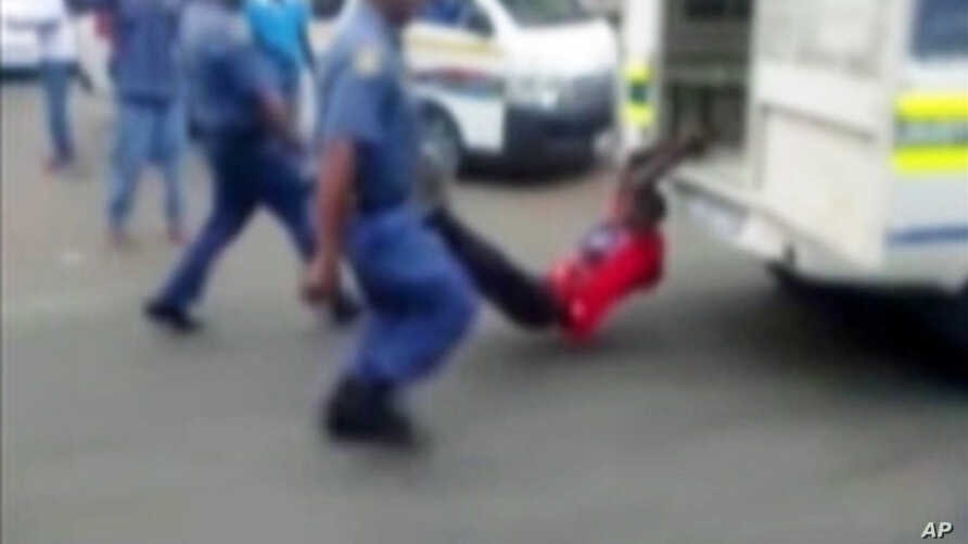 A South African man with his hands tethered to the back of a police vehicle being dragged behind as police hold his legs up and the vehicle apparently drives off, east of Johannesburg Feb. 26, 2013. The man died of his injuries.