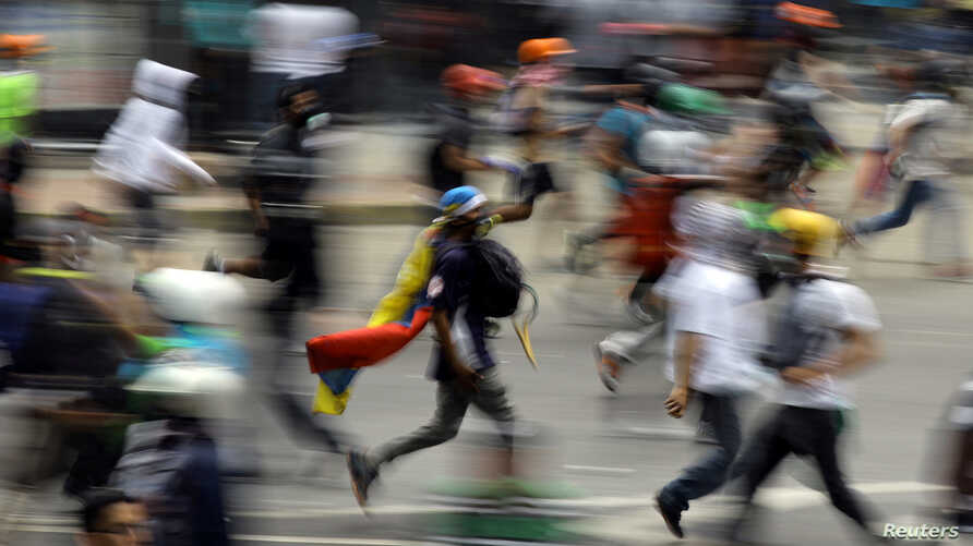 Demonstrators run during clashes with riot security forces at a protest against Venezuelan President Nicolas Maduro's government in Caracas, Venezuela, May 30, 2017.