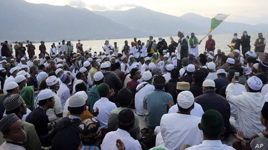 Indonesian Muslim men pray during a special prayer for the victims of earthquake and tsunami at Talise beach in Palu, Central Sulawesi, Indonesia, Oct. 5, 2018.