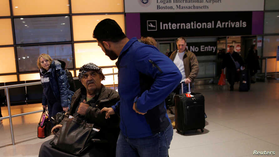 Mohanmmed (R) greets his father Jasim (C), who arrived on a flight from Doha, Qatar after U.S. President Donald Trump's executive order travel ban at Logan Airport in Boston, Massachusetts, Jan. 30, 2017.