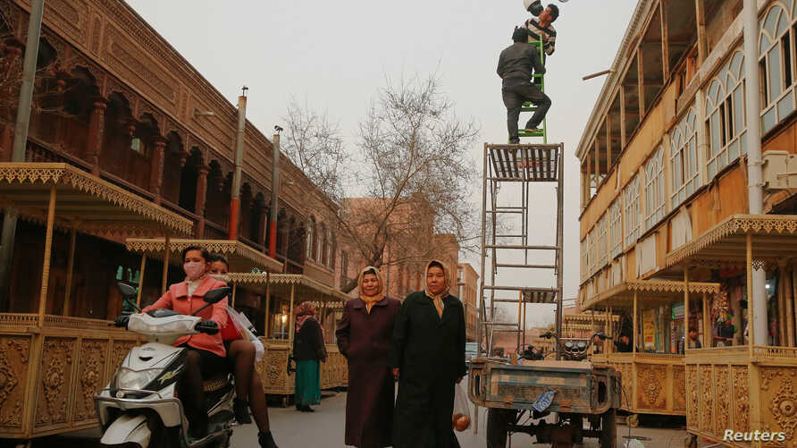 Men install a camera in a shopping street in the old town of Kashgar, Xinjiang Uighur Autonomous Region, China, March 23, 2017.