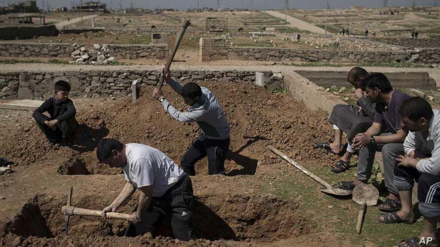 Relatives and friends dig the graves of two civilians killed during fighting between Iraqi security forces and Islamic State militants on the western side of Mosul, Iraq, March 25, 2017.