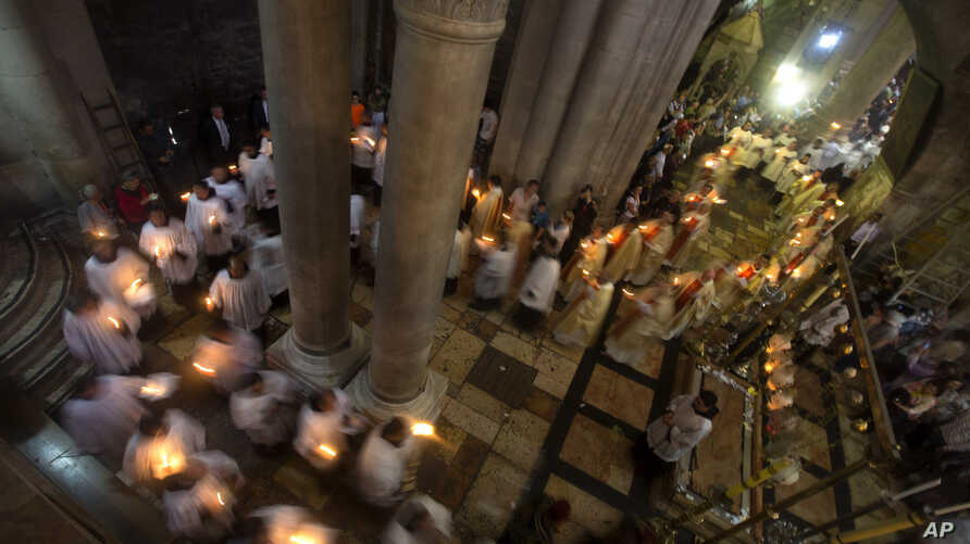 Christian clergymen hold candles during the Easter Sunday procession at the Church of the Holy Sepulchre, traditionally believed by many to be the site of the crucifixion and burial of Jesus Christ, in Jerusalem's Old City, April 20, 2014.