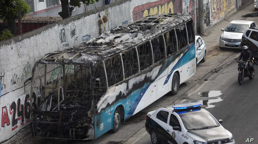 The shell of a bus is parked on the side of a road, allegedly set on fire by drug traffickers, in Rio de Janeiro, Brazil, Tuesday, May 2, 2017. Several public buses and cargo trucks were torched.