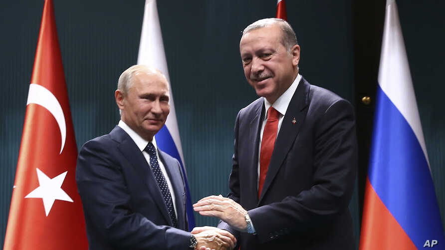 Turkey's President Recep Tayyip Erdogan, right, and Russian President Vladimir Putin shake hands after a joint news conference in Ankara, Turkey, Sept. 28, 2017.