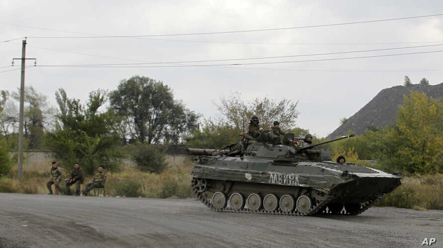 Pro-Russian gunmen sits atop armored personal carrier as they pass through the  checkpoint near the town of Zhdanivka, eastern Ukraine, Sept. 23, 2014.