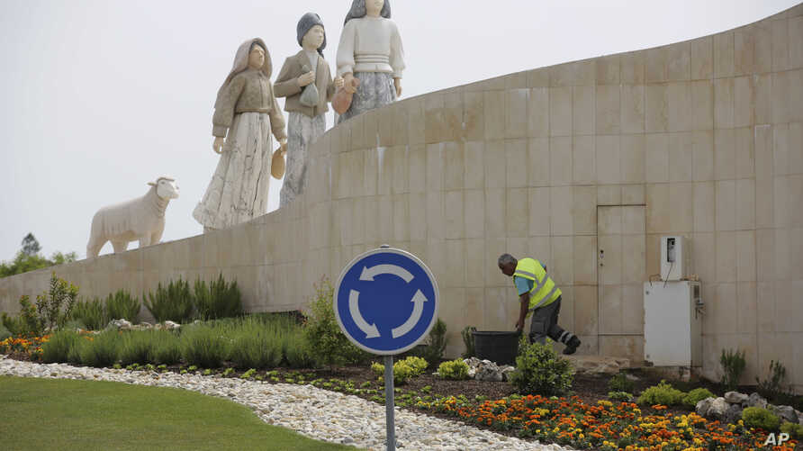 A gardener tends to the flowers on a roundabout underneath a statue of the three shepherd children who say they saw visions of the Virgin Mary 100 years ago, in Fatima, Portugal, May 4, 2017.