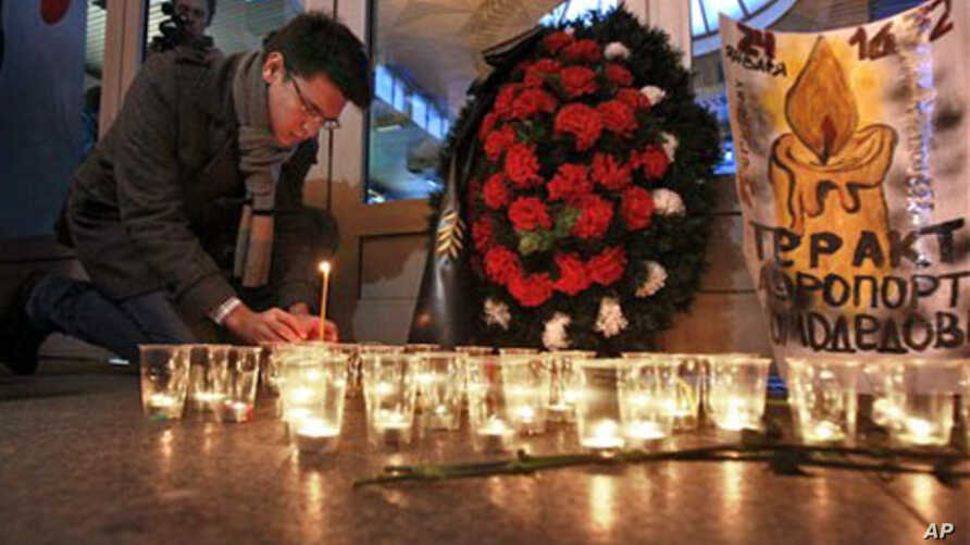 A man lights a candle at the Moskovsky railway station in St.Petersburg, Russia to commemorate the victims of a suicide bombing at Moscow's Domodedovo airport, January 25, 2011