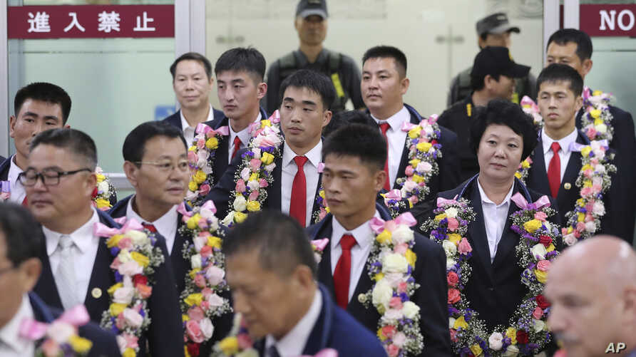 FILE - In this June 23, 2017, file photo, North Korean taekwondo demonstration team members and other officials arrive at Gimpo International Airport in Seoul, South Korea. Many in South Korea, including President Moon Jae-in, hope to use next year's