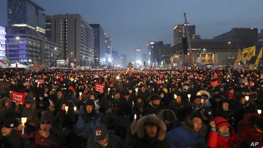 "Protesters hold candles during a rally calling for South Korean President Park Geun-hye to step down in Seoul, South Korea, Dec. 24, 2016. The letters read ""Arrest, Park Geun-hye."""