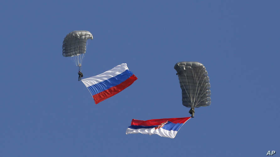 Serbian soldiers parachute from a transport helicopter with Russian, left and Serbian flags during the Russian-Serbian joint antiterrorist exercise Srem 2014, at Nikinci training ground, 60 kilometers west of Belgrade, Serbia, Nov. 14, 2014.