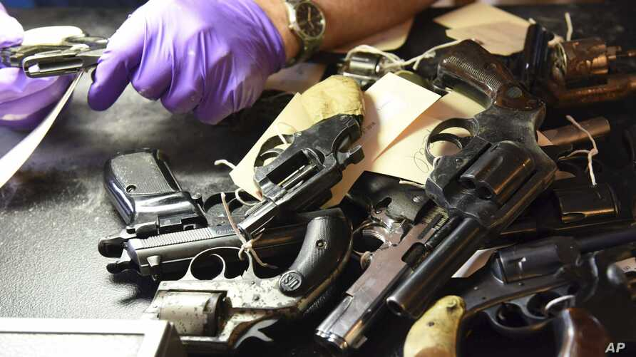 FILE - Forensic firearms examiners inspect weapons turned in by residents in a gun buy-back program co-sponsored with the New Life Covenant Church Southeast in the 6th Police District, in this June 2, 2018, photo provided by the Chicago Police Depart