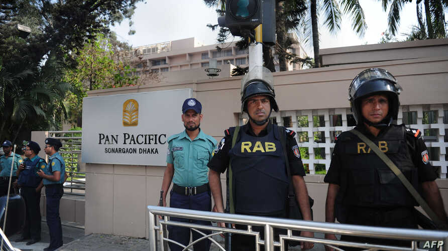 Bangladeshi policemen stand guard in front of the hotel where the visiting Indian President Pranab Mukherjee is staying in Dhaka, March 4, 2013.