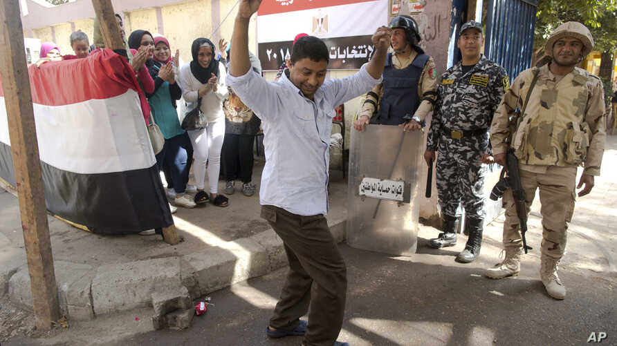 A man dances as women sing national songs in front of a polling station during the second day of the presidential in Cairo, Egypt, Tuesday, March 27, 2018. Egyptians were voting Tuesday on the second day of a lackluster election that President Abdel-...