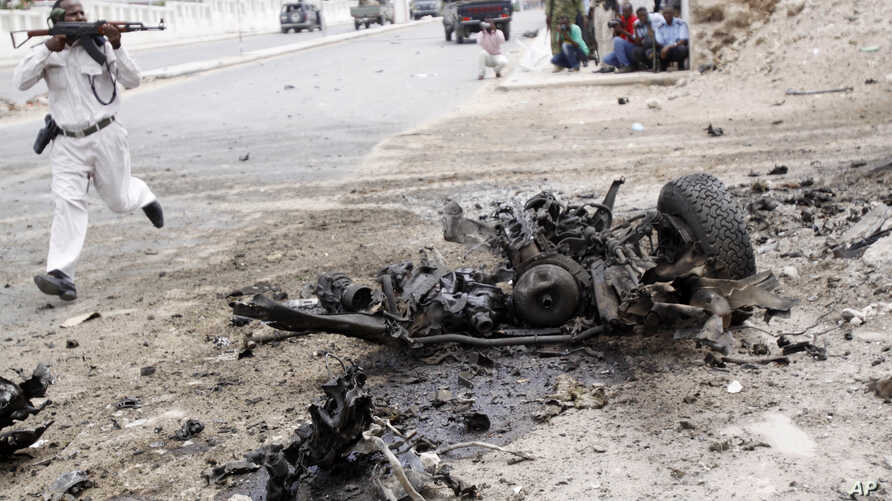 A Somali soldier runs to fight near the wreckage of a car bomb during an attack on Somalia's parliament, Saturday, May 24, 2014.
