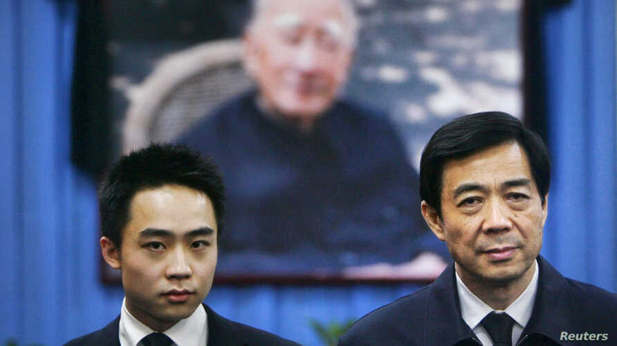 China's former Chongqing Municipality Communist Party Secretary Bo Xilai (R) and his son Bo Guagua stand in front of a picture of his father Bo Yibo, former vice-chairman of the Central Advisory Commission of the Communist Party of China. (File photo