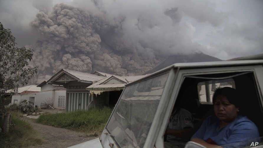Residents ride in a truck as Mount Sinabung releases pyroclastic flows during its eruption in Karo, North Sumatra, Indonesia, Wednesday, Aug. 2, 2017.
