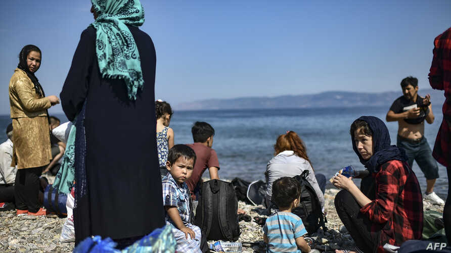 FILE - Migrants from Afghanistan arrive after crossing the Aegean Sea from Turkey with a dinghy on the Greek Mediterranean island of Lesbos on Aug. 6, 2018.