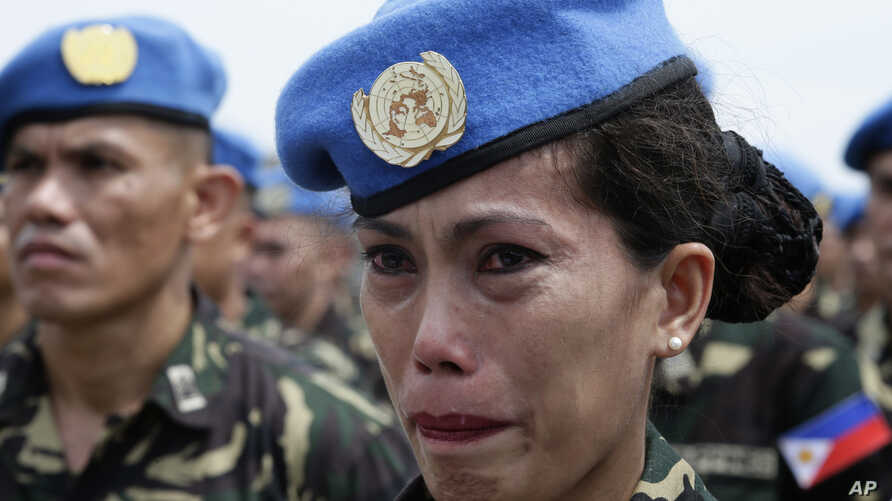 Philippine Navy Petty Officer 2 Ellen Paculba, one of 157 Philippine troops who are to be deployed in Haiti as U.N. Peacekeepers, cries during sendoff ceremony, Sept. 22, 2014.