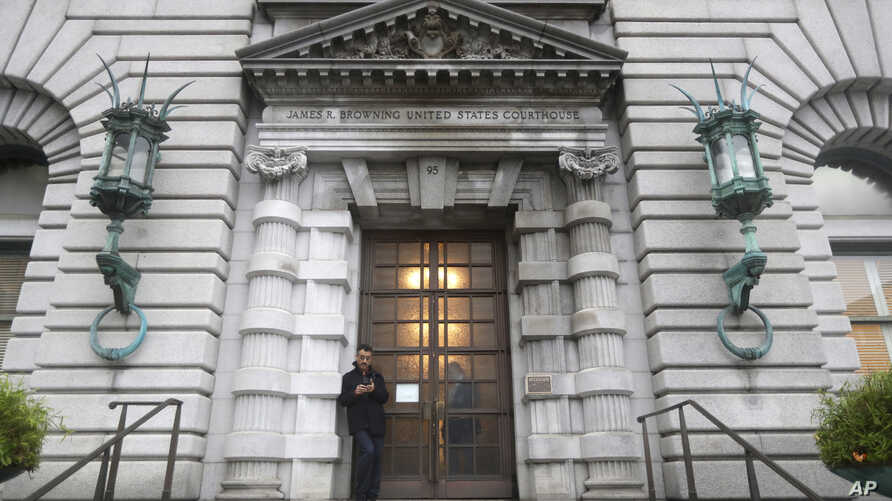 FILE - A man stands outside the main door of the 9th U.S. Circuit Court of Appeals building in San Francisco, Feb. 9, 2017.