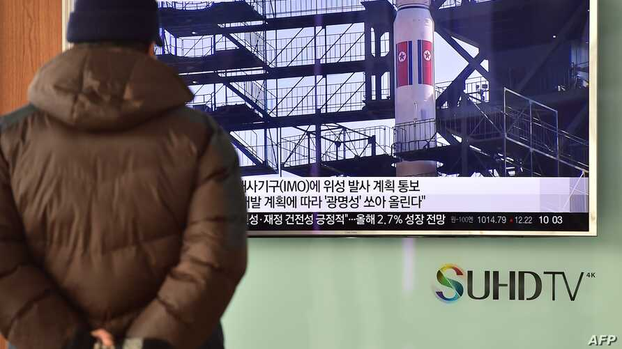 A man watches a news report on North Korea's planned rocket launch as the television screen shows file footage of North Korea's Unha-3 rocket which launched in 2012, at a railway station in Seoul, Feb. 3, 2016.
