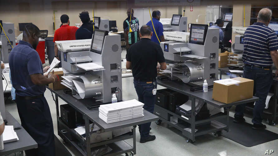 Workers load ballots into machines at the Broward County Supervisor of Elections office during a recount on Nov. 11, 2018, in Lauderhill, Florida.