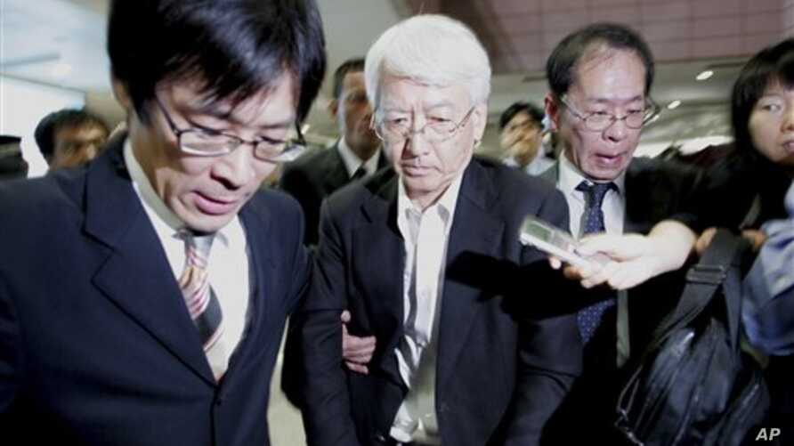 One of three Japanese, center, who had been detained by Chinese military and released today, is escorted by company's officials upon arrival at Pudong International Airport in Shanghai, 30 Sep 2010