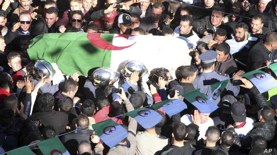 The coffin of Hocine Ait Ahmed, who spent nearly a quarter-century in exile in Europe, is carried during a burial ceremony in his native village, Ath Ahmedh, Algeria, Jan.1, 2016.