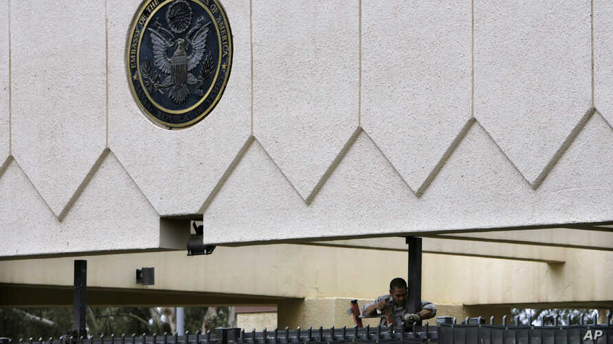 In this Thursday, Sept. 18, 2008 file photo, a worker repairs the damaged gate of the main entrance of the US embassy in the capital Sanaa, Yemen.