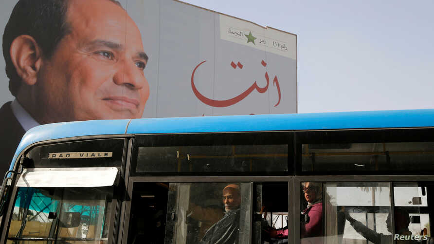 FILE - People ride on a bus as posters with Egypt's President Abdel Fattah al-Sissi are displayed in Cairo, Egypt, March 25, 2018.