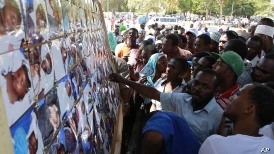 Relatives jostle to identify the bodies of their relatives who perished in a ferry tragedy that occurred on its way to Pemba on a picture board at the Maisara grounds in Zanzibar, September 11, 2011.