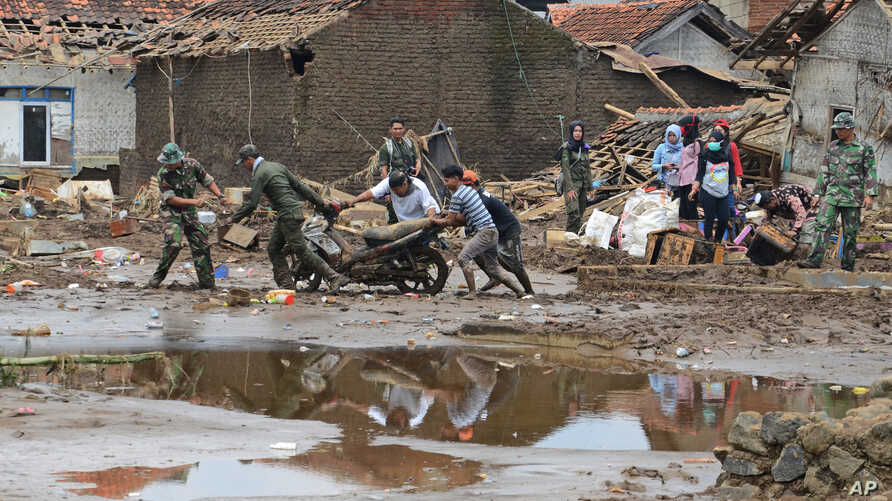 Rescuers pull a motorbike through the mud at a village badly hit by flash flood in Garut, West Java, Indonesia, Sept. 22, 2016.
