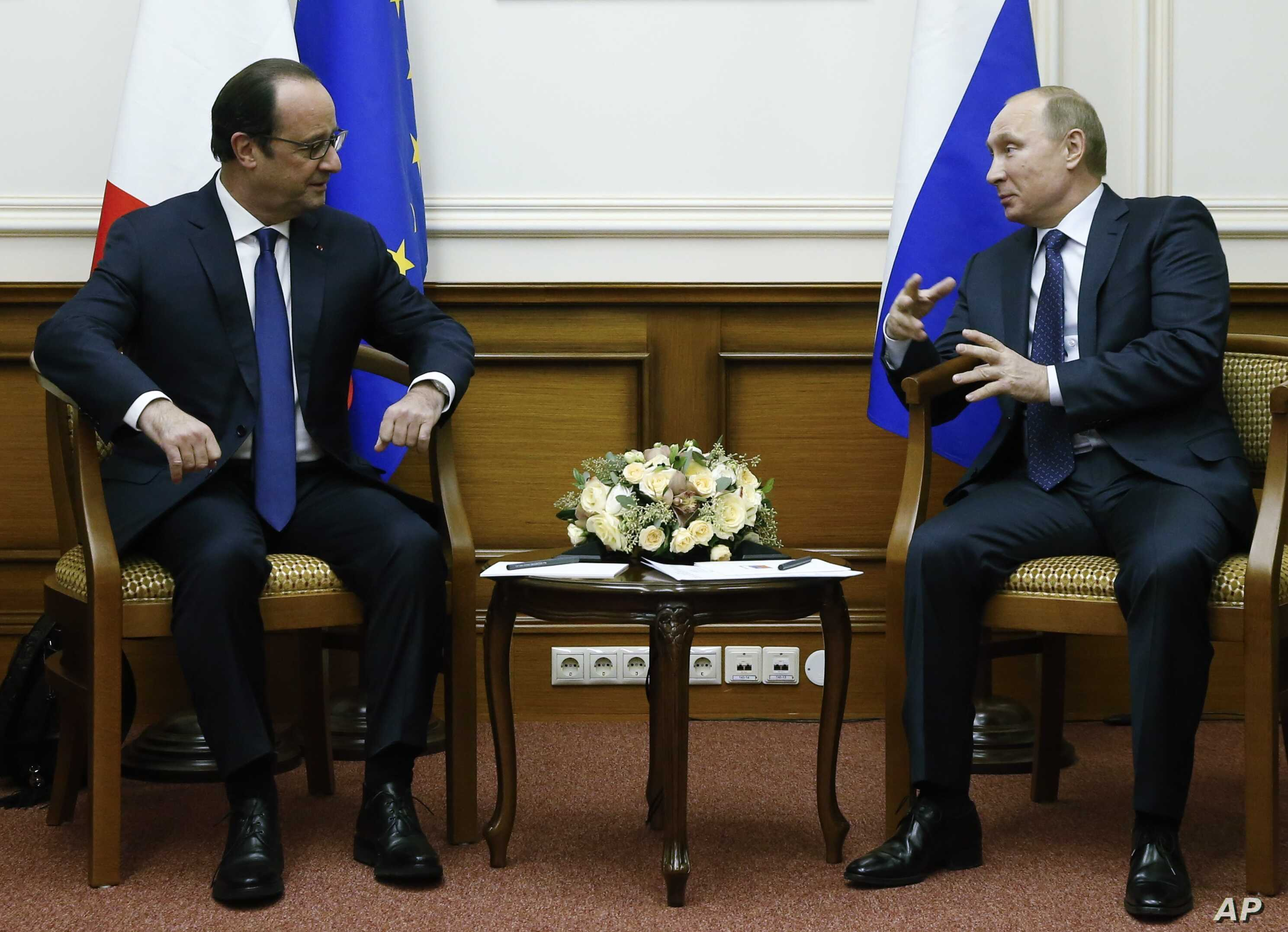 Russian President Vladimir Putin, right, and French President Francois Hollande speak during their meeting at Moscow's Vnukovo airport, Saturday, Dec. 6, 2014.