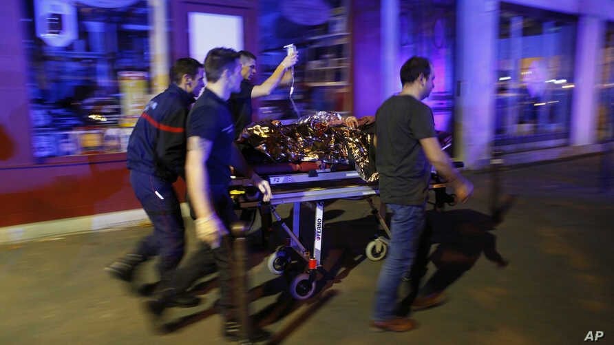 FILE - In this Nov. 14, 2015, photo, a person is being evacuated after a shooting, outside the Bataclan theater in Paris.
