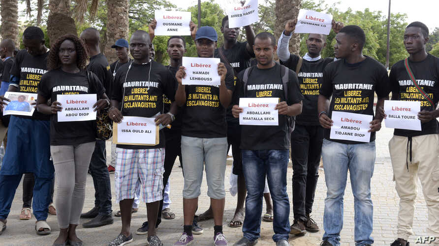 FILE -  Anti-slavery militants demonstrate, Aug. 3, 2016, in Dakar against the imprisonment of fellow activists in Mauritania as they hold placards with their names.