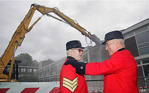 Chelsea pensioners Bill Lunsden, left, is comforted by colleague Paddy Fox as they watch the demolition of the old infirmary at the Royal Hospital Chelsea in west London. The Old Infirmary of the Royal Hospital Chelsea is being demolished to moderniz