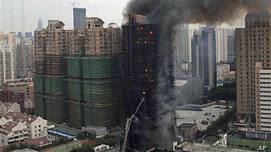 Firefighters spray water on an apartment building on fire in the downtown area of Shanghai, east China, on 15 Nov 2010