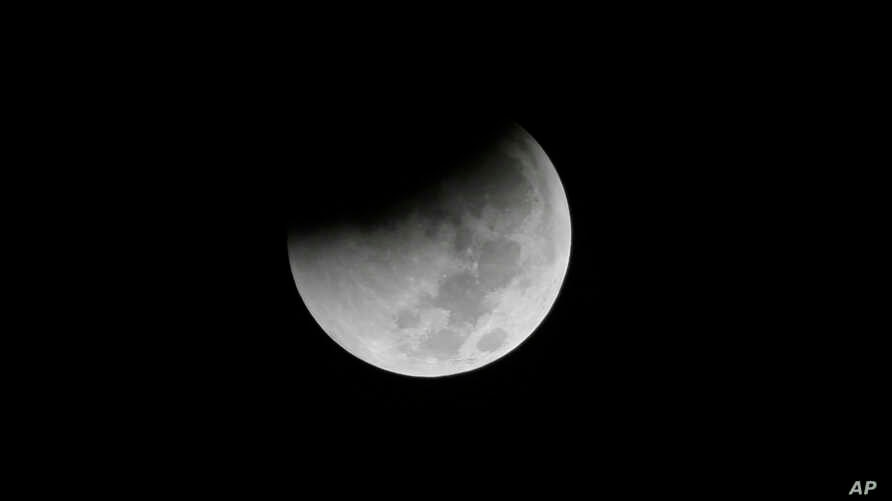 FILE - Earth starts to cast its shadow on the moon during a complete lunar eclipse seen from Jakarta, Indonesia, Aug. 28, 2018.